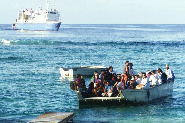 Passengers arriving in Tokelau off a ferry from Samoa. There is no harbour in Tokelau, so passengers need to take a landing barge across the reef to get to shore. Photo: New Zealand Ministry of Foreign Affairs and Trade